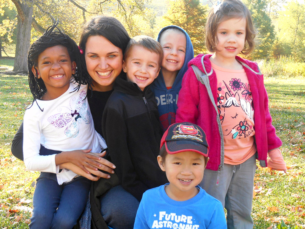 Group of CID preschool children pose with their teacher on a sunny fall day