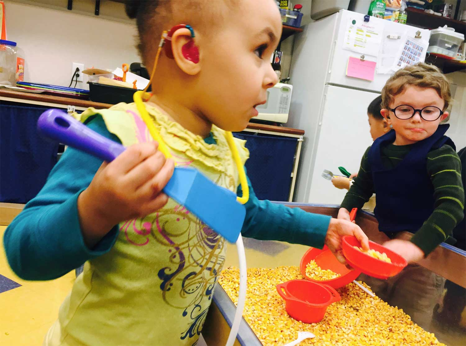 young child with hearing aid sandbox of popcorn