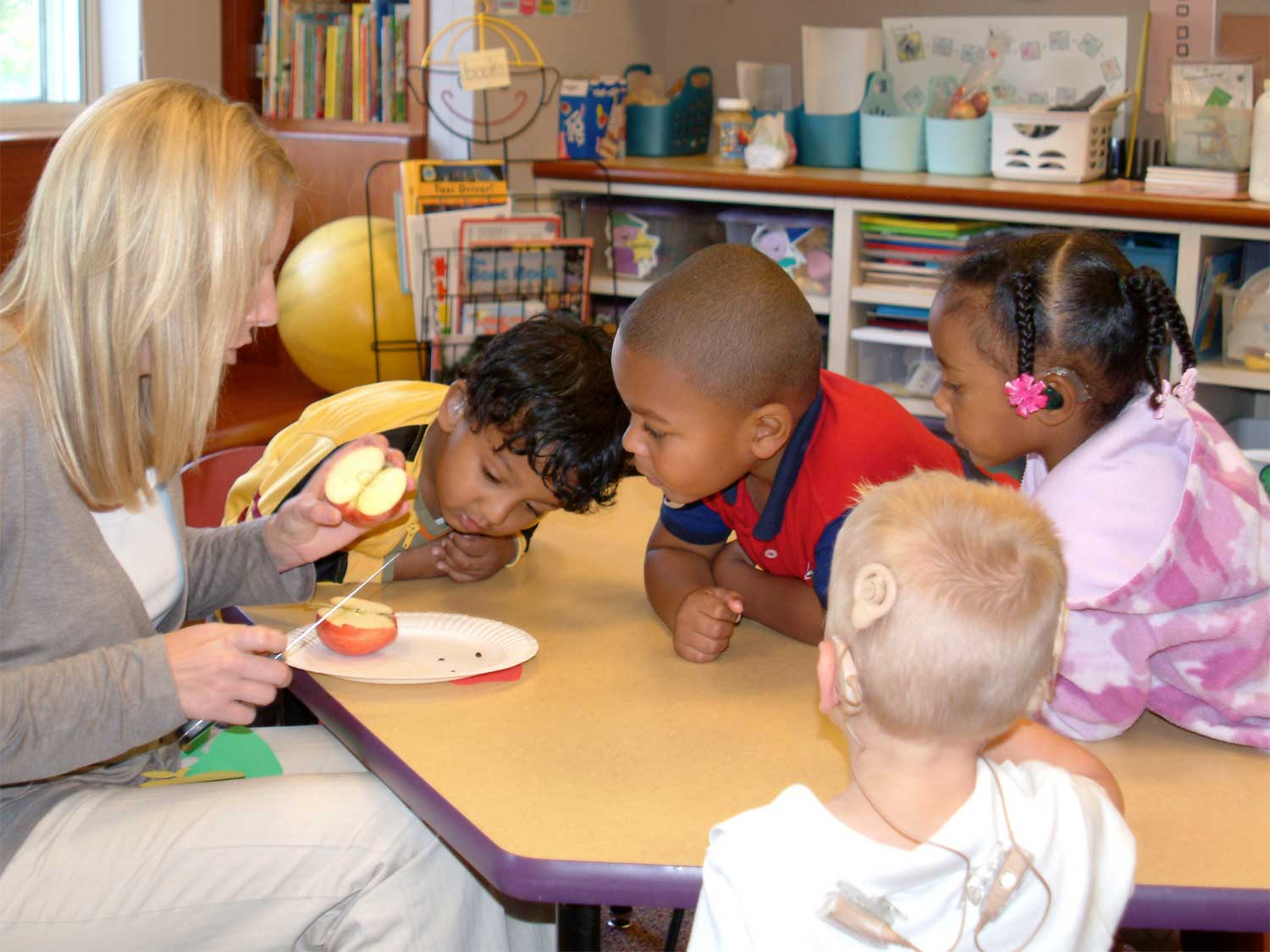 teacher cutting apples with pre-k children