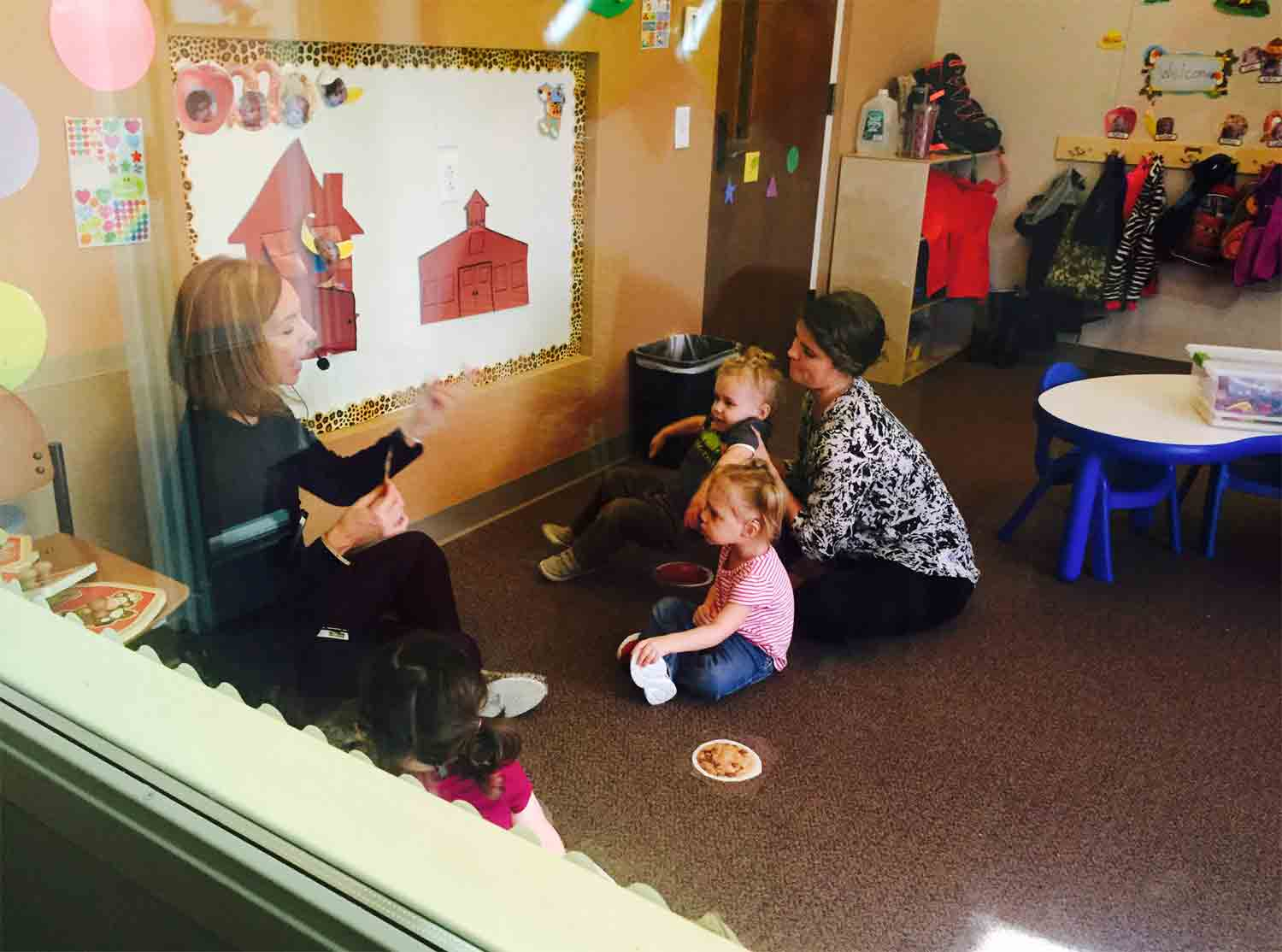 Looking through observation window at small group toddler class