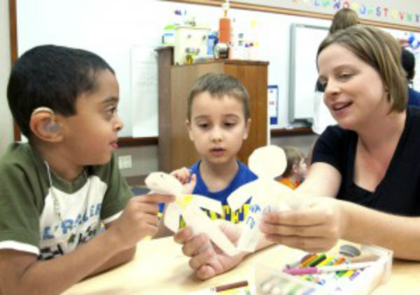 Two boys cutting figures with occupational therapist in CID pre-k