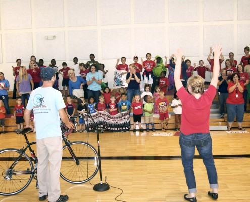 Jacob brings his bicycle to the gym to rally the CID kids.