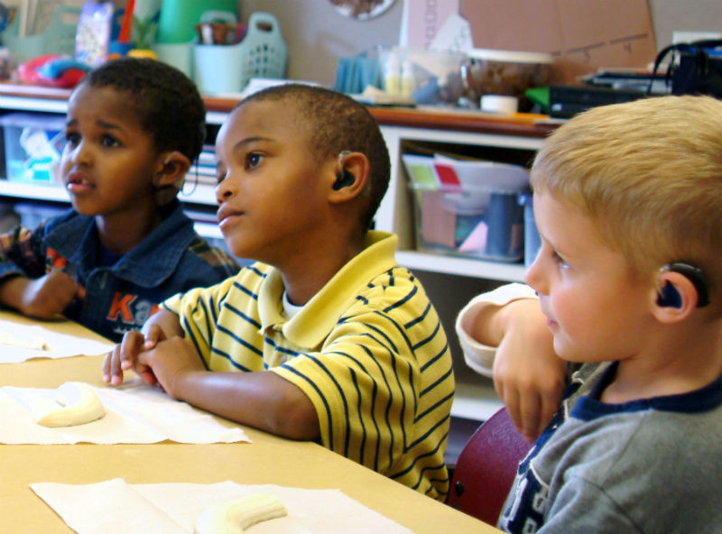 Three young deaf boys paying attention in class