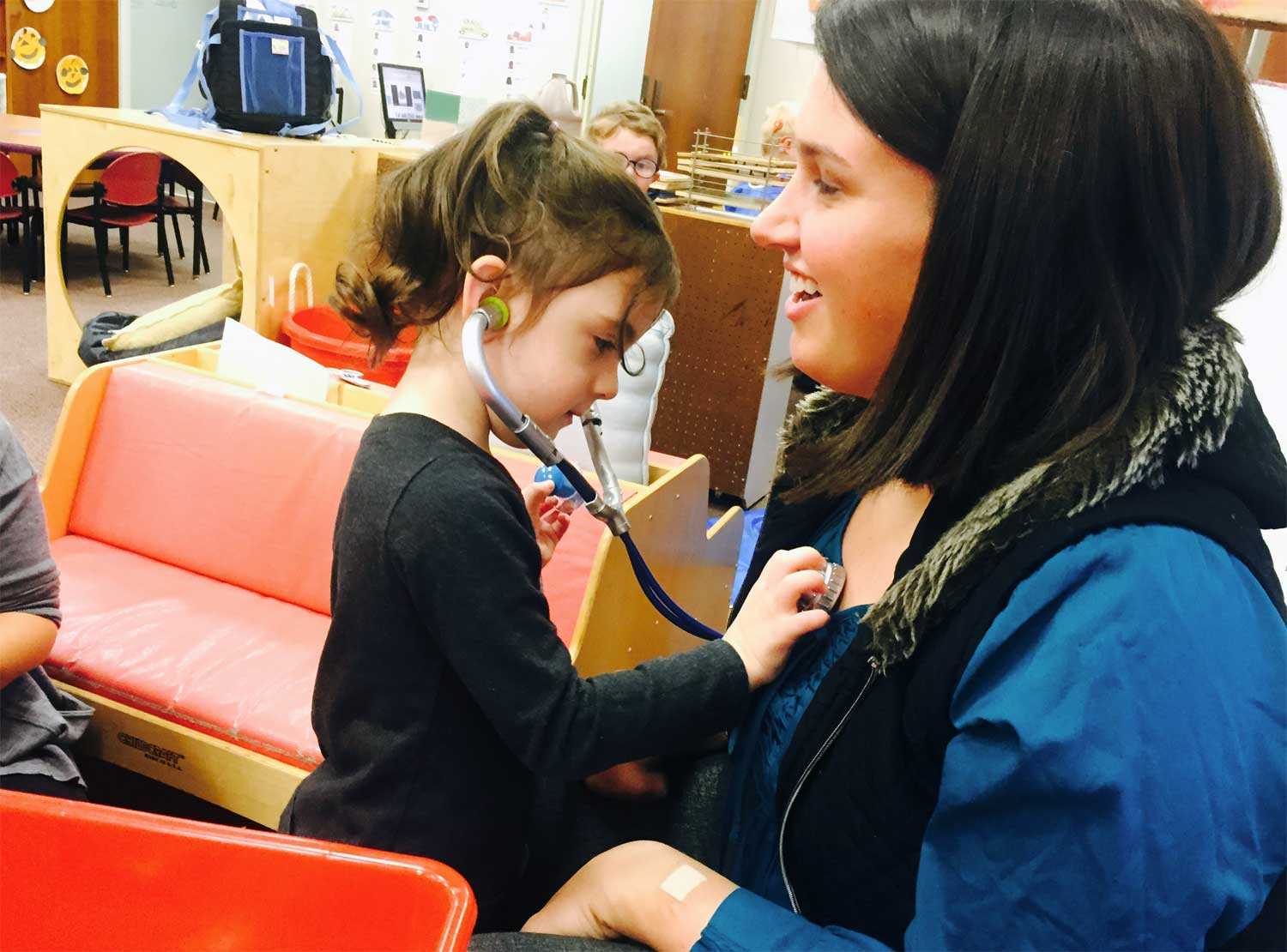 A young student uses a play stethoscope to listen to her teacher's heart.