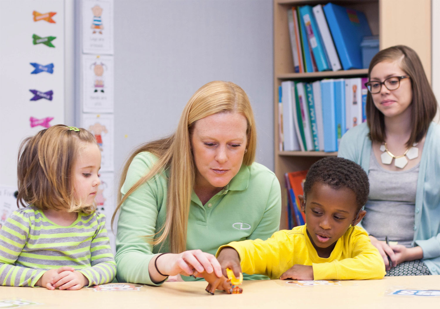 CID teacher teaching a language less to two preschoolers as an observer watches.