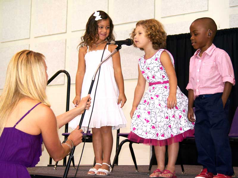 Young girl speaking into microphone at CID graduation