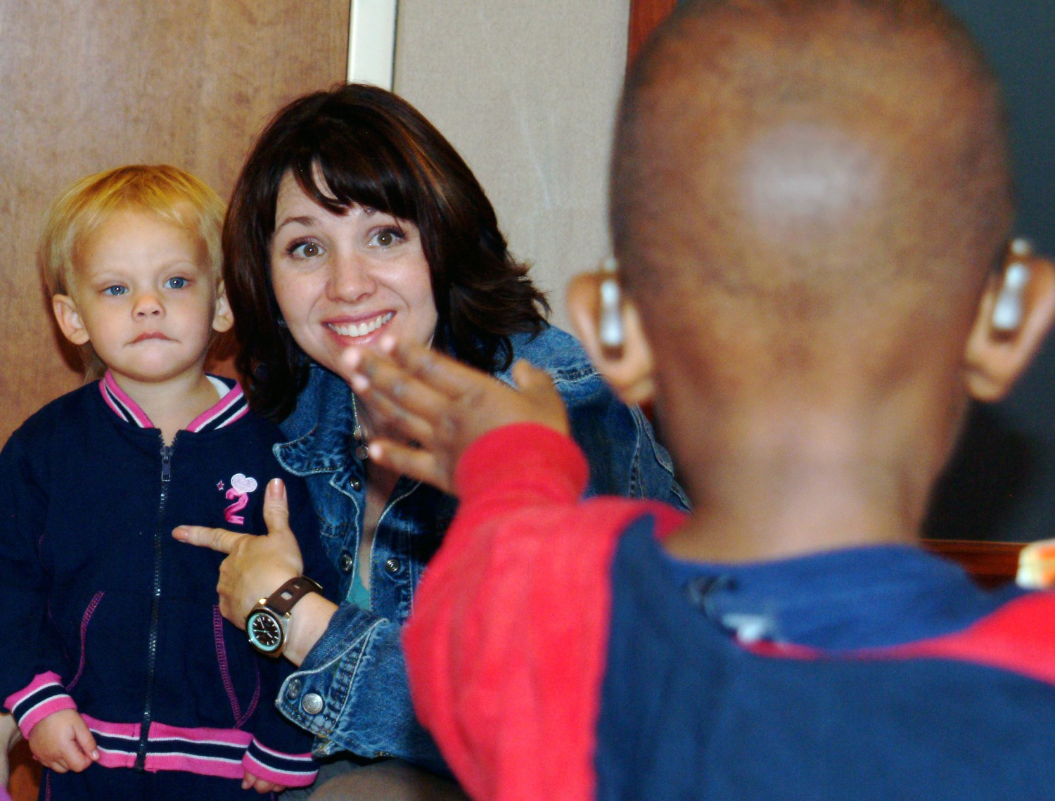 toddlers with hearing aids interact with their teacher at CID