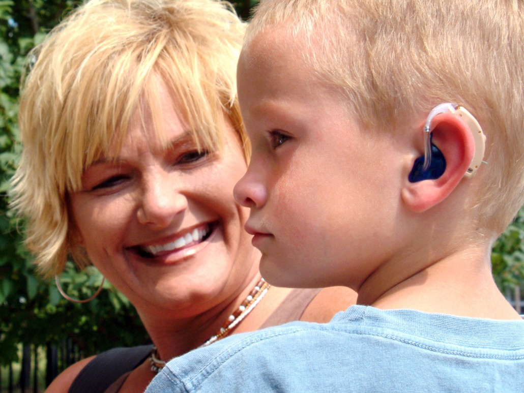 Young man with a hearing aid and his mom
