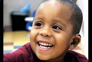 smiling boy with hearing aids