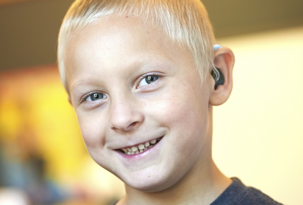 smiling deaf boy with hearing aid