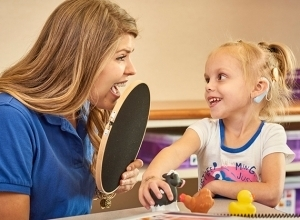 A teacher uses an auditory hoop and farm animal toys to help a child with a cochlear implant to learn to listen.